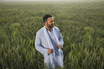 Indian man looking away while standing in a field