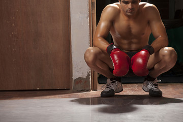 Tired male boxer crouching in gym