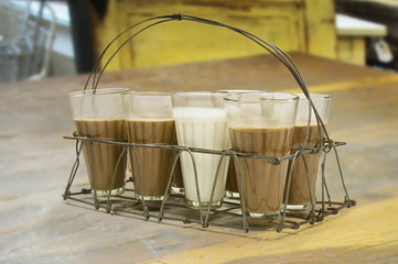 Glass of milk kept among chai in metal grid tray on a wooden surface