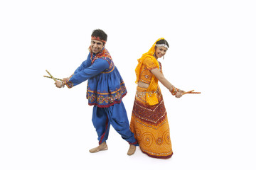 Full length of an Indian couple in traditional wear performing Dandiya Raas over white background