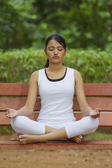 Young woman in lotus position meditating