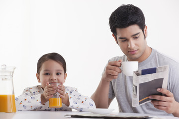 Little girl drinking juice while father reading newspaper