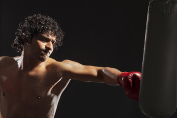 Boxer about to hit punching bag over black background