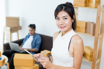 Young Asian Woman Using Tablet for Work at Home, Young Owner Woman Start up for Business Online, SME, Delivery Project, Woman with Online Business or SME Concept.