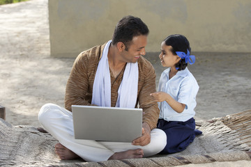 Happy father with his little daughter using laptop
