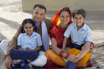 Portrait of a happy Indian family sitting on cot