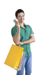 Portrait of young man with shopping bag and credit card