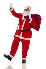 Full length of Santa Claus carrying sack of presents with bell over white background