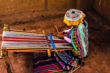 Peruvian woman weaving colorful alpaca wool, using ancient techniques