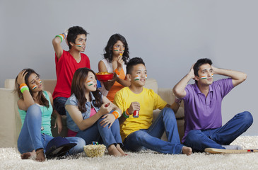 Young friends reacting with disappointment while watching cricket match