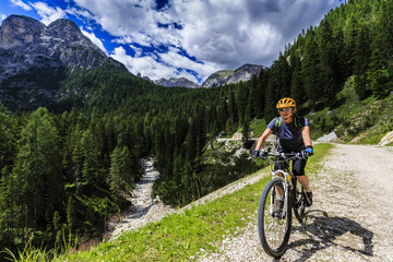 Mountain biking woman along river in Dolomites, Italy