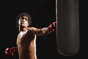 Male boxer hitting heavy bag