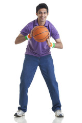 Full length portrait of young man holding basketball over white background