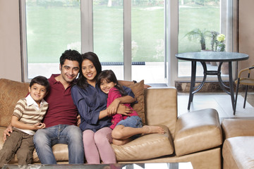 Portrait of happy young parents sitting with children on sofa at home
