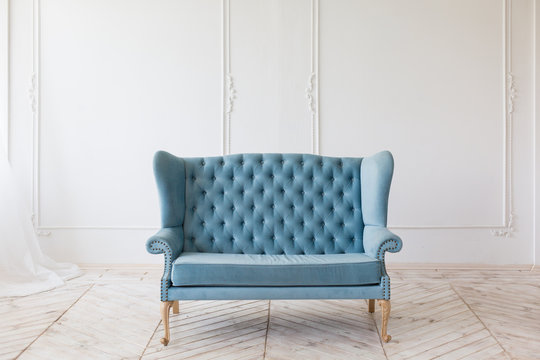 Blue soft sofa in white interior with fabric upholstery