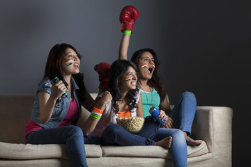 Enthusiastic young female friends watching boxing match together at home