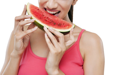 Midsection of young woman taking a bite from slice of watermelon