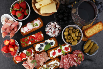 Italian antipasti wine snacks set. Cheese variety, Mediterranean olives, pickles, Prosciutto di Parma, tomatoes and wine in glasses. Spanish tapas