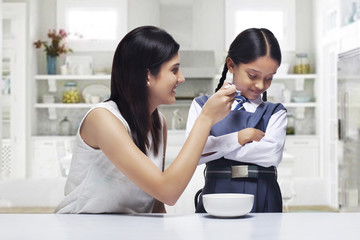 Mother trying to feed daughter breakfast