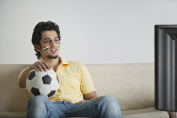 Young man in casuals with face painted watching television while holding soccer ball
