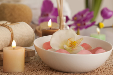 Flowers in a bowl with candles and bath scrub