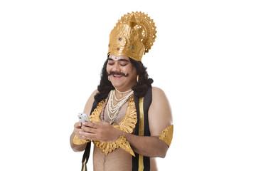 Man dressed as Raavan reading an sms