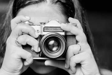 Portrait of young woman taking photos with vintage retro camera. Black and white