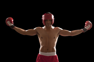 Portrait of confident male boxer standing with arms outstretched isolated over black background