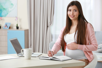Beautiful young pregnant woman working at home