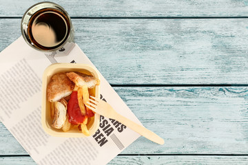 Fried fish and chips with glass of juice on wooden background