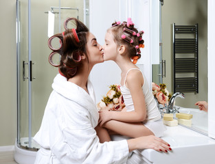 Young mother and daughter in curlers in a bath room happy smiling kissing girl