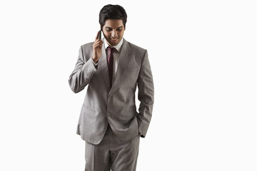 Handsome young businessman on call over white background