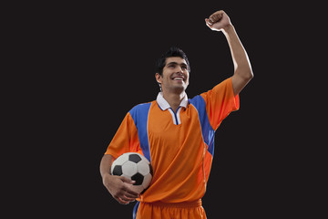 Happy young man in sports clothing celebrates victory while holding ball over black background