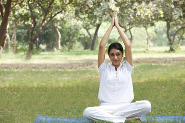 Young woman doing yoga with arms raised