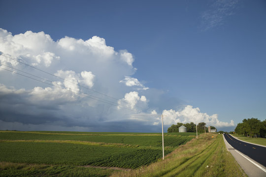 Rural midwest road and fields under big clouds