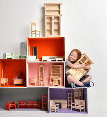 Red hair Baby Girl Kid playing with doll house stuffed with mini furniture toys