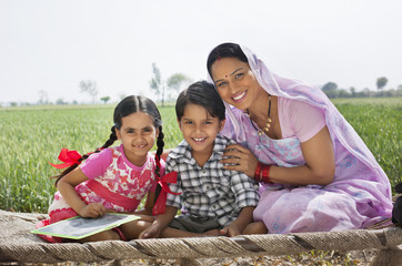 Portrait of a happy mother sitting with her children on cot