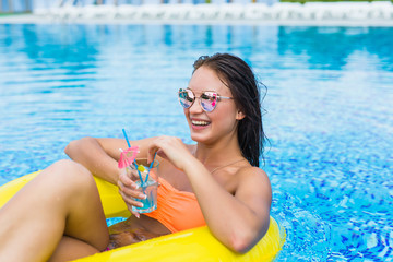 Young woman enjoying with rubber ring and cocktail in swimming pool