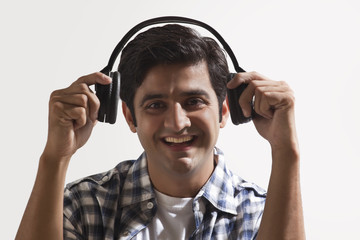 Smiling young man wearing headphones over colored background