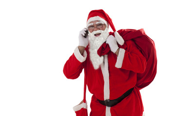 Front view of Santa Claus carrying sack while talking on cell phone