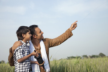 Father and son flying a kite in field