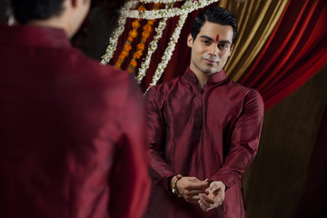 Mirror reflection of young Indian bridegroom getting dressed