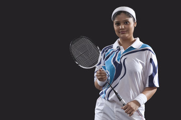 Portrait of young female player holding badminton racket isolated over black background