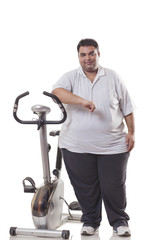 Full length of an obese man standing by an exercise bike over white background