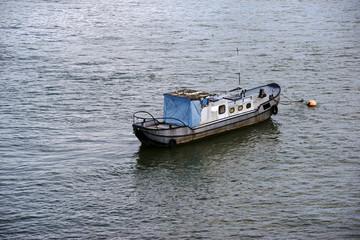 Der alte Kahn  / Ein altes Boot mit verrosteten Seitenwänden und einer zugedeckten Kajüte ankert am Ufer eines Flusses.