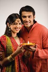 Couple holding a diya
