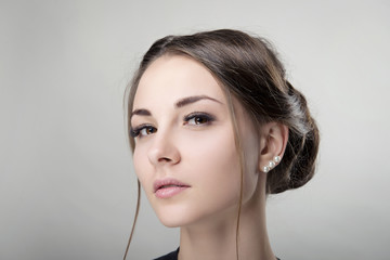 Portrait of young brunette woman with clean skin and daily makeup and hairdo bun on an isolated background