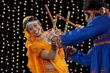Portrait of happy young woman performing Dandiya Raas with man against neon lights