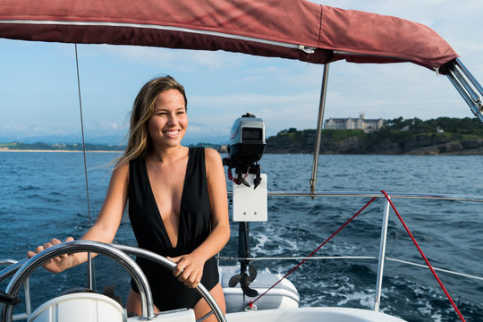 Smiling woman steering yacht