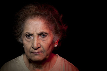 Close-up of serious woman over black background